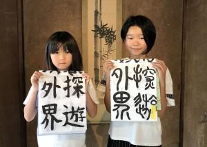 自由研究で百字文を完成させた二人。左は楷書、右は篆書の「探遊外界」。
